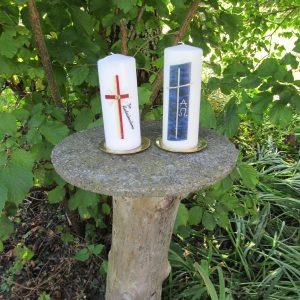 Erinnerungskerzen mit rotem Kreuz und goldenem Kreuz auf blauem Hintergrund