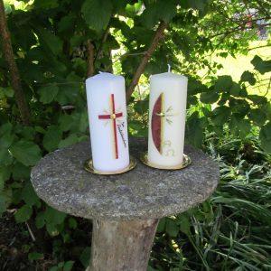 Erinnerungskerzen mit rotem Kreuz und mit goldenem Kreuz und halbrotem Hintergrund